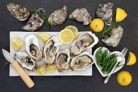 aphrodisiac: Oysters on crushed ice with oyster knife and silver fork with lemon fruit and samphire  in a porcelain dishes on a slate.