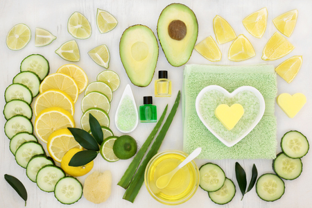 toweling: Ingredients for skin care beauty treatment with cucumber, aloe vera, avocado and citrus fruit with essential oil, exfoliating salt and flannels on distressed white wood background. Stock Photo