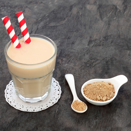 Maca root heath drink in a glass with powder in a white china bowl and spoon.