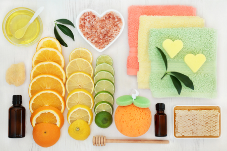Skin and body care products with citrus fruit, honey, essential and almond oil, himalayan salt and spa accessories on white distressed background.