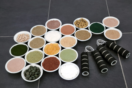 casein: Body building powders and supplements in porcelain bowls with hand grippers over slate background.