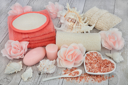 cosmetic product: Cleansing spa accessories with himalayan salt, rose soap petals and exfoliating bathroom products on distressed white wood background. Stock Photo