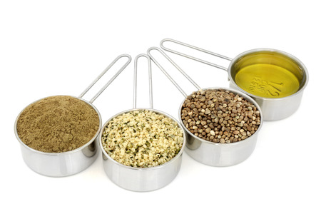 dried food: Hemp health food ingredients with powder, hulled seed, dried seeds and oil in metal measuring scoops on white  background.