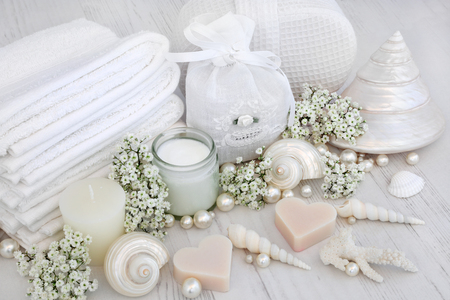jabon: Luxury spa products with white face towels, sponge, cream and flowers with shells and pearls over distressed wood background. Foto de archivo