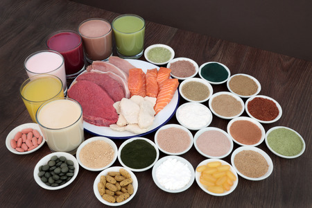 casein: Health food and drinks for body builders with lean meat of steak, chicken and pork with salmon and dietary supplemment powders and vitamin pills on oak background. Stock Photo