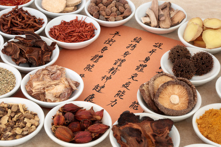 Traditional chinese herb selection used in herbal medicine in porcelain bowls with calligraphy script. Translation describes the medicinal functions to maintain body and spirit health and balance energy.