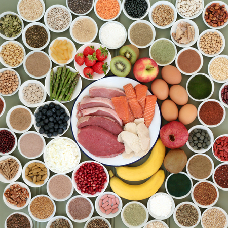 Large health food selection for body builders with meat, salmon, dairy, fruit, nuts, pulses, seeds, cereals  and supplement powders forming a background. Stock Photo