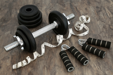 hand gripper: Body building equipment with dumbbell weights, hand grippers and tape measure over marble background. Stock Photo