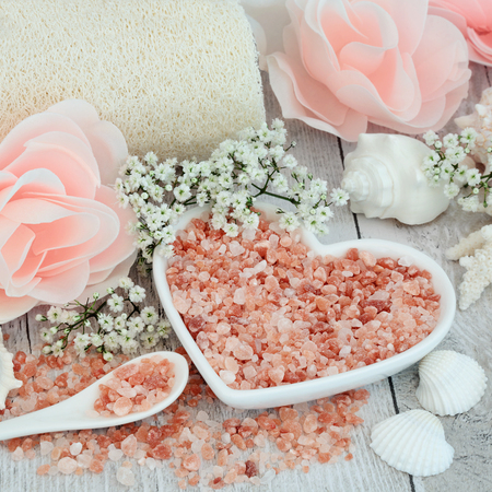 Himalayan sea salt for skin care and detoxifying with exfoliating loofah, rose flower soap petals, shells and gypsophilla flowers.