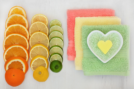 fruit background: Citrus spa ingredients with orange, lemon and lime fruit, bath crystals and soap in heart shaped dish with flannels on distressed wood background. Stock Photo