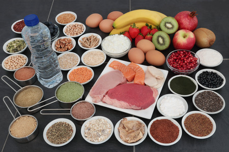 Body building food of high protein lean meat and salmon, supplement powders, fruit, nuts, seeds, grains,  pulses, herbs, dairy and bottled water over slate background.