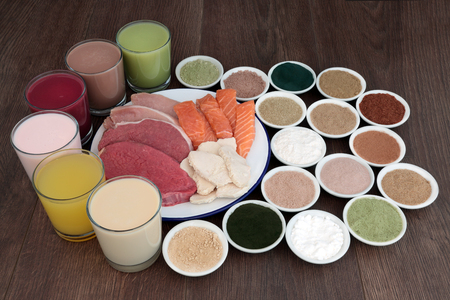 Health food and drinks for body builders with lean meat of steak, chicken and pork with salmon and dietary supplemment powders on oak background.