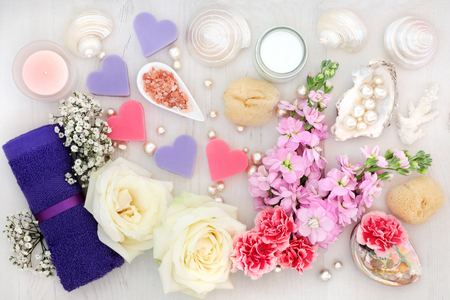 Bathroom and spa accessories with white rose, pholx and gypsophilla flowers, himalayan salt, moisturising cream, face towel, soaps, shells and pearls on distressed wood background. Stock Photo