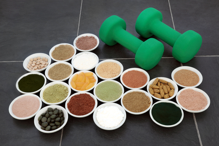 Body building powders, vitamin supplement pills and dumbbell weights over slate background.