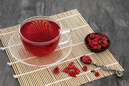 teas: Pomegranate herb flower tea in a glass cup, wooden bowl and old spoon on a bamboo mat. Stock Photo