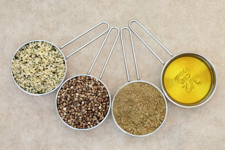 dried food: Health food of hulled hemp seed,  dried seeds, powder and oil in measuring scoops on natural hemp peper background. Left to right. Stock Photo