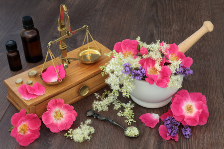 Naturopathic alternative medicine with rose, lavender and meadowsweet flowers with essential oil bottles and old brass apothecary scales.