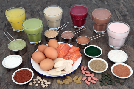 Health food and health drinks for body builders with high protein meat, fish, eggs and supplement powders with vitamin pills. Stock Photo