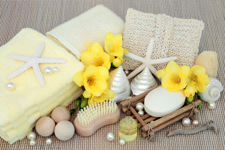 toweling: Natural spa beauty cleansing products with freesia flowers, shells and pearls on bamboo background. Stock Photo