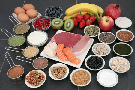 Health food for body builders with lean meat, salmon, dairy, fruit, supplement powders, herbs, pulses, nuts, cereals and seeds on slate background. Stock Photo - 74520855