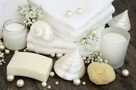 White body care and bathroom accessories with moisturizing cream, soap, white flannels, natural sponge, candle, mother of pearl shells and pearls.