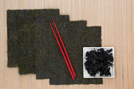 algas marinas: Nori japanese seaweed food in sheets with red chopsticks on bamboo and dried hijiki in a white china dish.