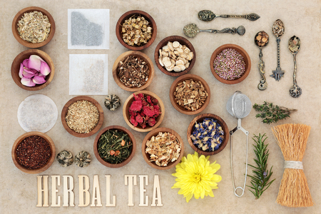 rooibos: Herbal tea selection with wooden letters, metal strainer and tea bags on natural hemp paper background. Stock Photo