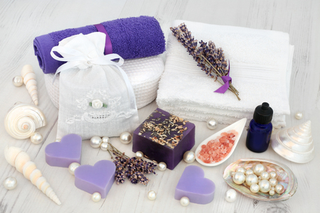 Lavender herb flowers with aromatherapy, spa and bathroom accessories, himalayan salt, soap, face towels  and decorative shells and pearls.