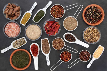 Dried herb and spice selection high in antioxidants and vitamins on slate background.