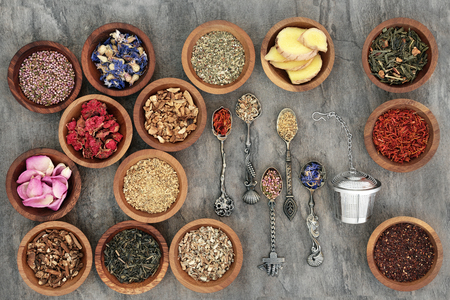 teas: Herb tea varieties in old spoons and wooden bowls with strainer, teas also used in natural alternative medicine.