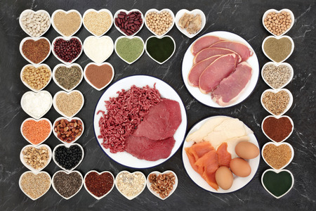 Large health food selection for body builders with supplement powders, meat, fish, herbs, pulses, nuts, seeds, cereals, grains and dairy in porcelain dishes.