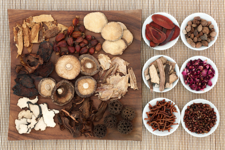 Chinese herb selection used in natural herbal medicine on maple wood board and in porcelain on bamboo background. Stock Photo