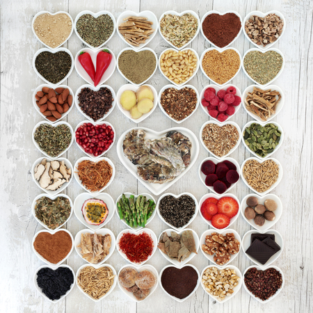 Aphrodisiac food sampler to promote sexual health in heart shaped china bowls over white distressed wood background.