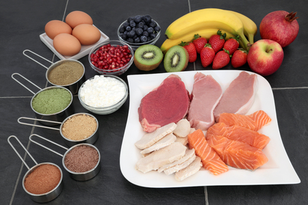 Body building food of supplement powders, high protein lean meat and salmon, fruit and dairy over slate background.