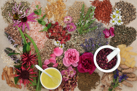 holistic view: Ingredients for skin care treatment with flower and herb selection, almond oil and rose petals in a mortar with pestle on hemp background. Stock Photo