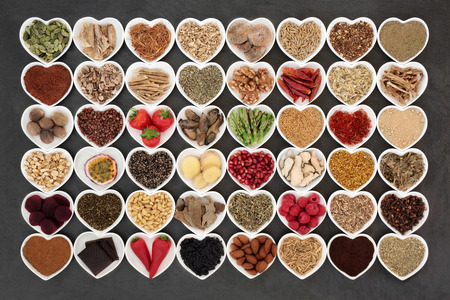 Aphrodisiac food sampler of foods to promote sexual health in heart shaped china bowls on slate background. Banco de Imagens