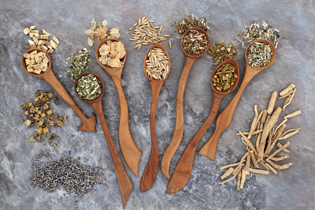 Herbs used in alternative herbal medicine for sleeping and anxiety disorders in wooden spoons.