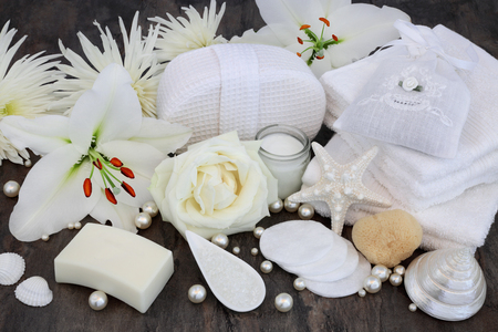 Rose and white lily flower cleansing skincare beauty treatment including moisturising cream, soap, flannels, salt, natural sponge with shells and pearls.