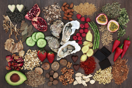 Aphrodisiac food to promote good sexual health on oak wood background.