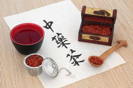 herb medicine: Chinese safflower herb tea with calligraphy on rice paper, tea cup, old wooden caddy box and spoon, also used in alternative herbal medicine. Translation reads as chinese herb tea.