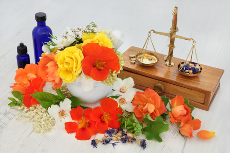 ladys mantle: Natural flower and herb therapy with elderflower, valerian, cornflower, nasturtium, orange blossom, rose,  marjoram and ladies mantle with old brass apothecary scales and essential oil bottles.