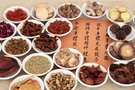 liquorice: Traditional chinese herbal medicine selection in porcelain bowls with calligraphy script. Translation describes the medicinal functions to maintain body and spirit health and balance energy. Stock Photo