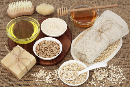 toweling: Skincare and body care products to cleanse and soothe skin disorders with oats, honey, oil, natural moisturiser and soap on hessian background.