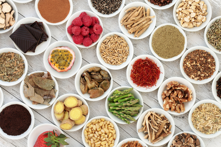 Aphrodisiac food sampler of foods to promote sexual health in china bowls on distressed wooden background. Banco de Imagens
