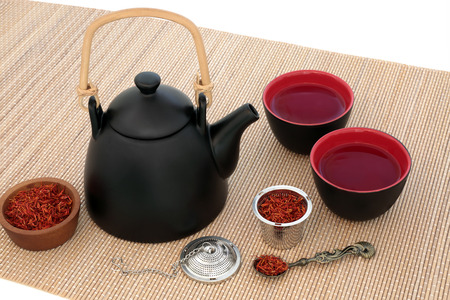 herb medicine: Safflower herb tea with oriental teapot and cups with strainer and old spoon on bamboo over white background. Used also in chinese herbal medicine.