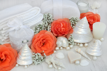 Skincare beauty cleansing products with orange rose flowers, soap, moisturising cream, cotton towelling accessories and decorative shells and pearls on rustic white wood background.