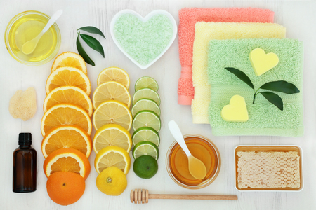 Productos de tratamiento de belleza Citrus spa con naranja, limón y lima, cristales de baño, esencia, esponja, miel, aceite de almendra, jabón con franelas sobre fondo de madera rústica.
