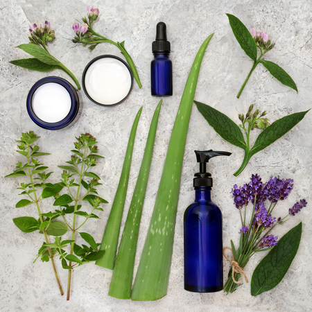 holistic view: Herbs, cream and oils to heal skincare disorders with comfrey, marjoram, aloe vera and lavender. Stock Photo