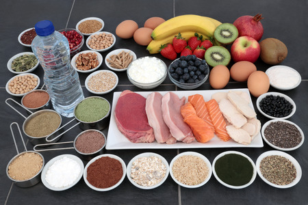 Body building health food of high protein lean meat and salmon, supplement powders, fruit, nuts, seeds, grains,  pulses, herbs, dairy and bottled water over slate background.