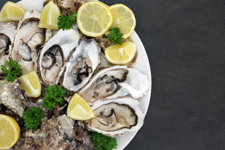 Oyster aphrodisiac food on a porcelain plate with lemon fruit and parsley herb on slate background.